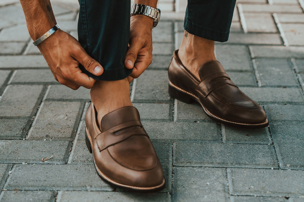 man wearing brown leather loafers with tailored pants